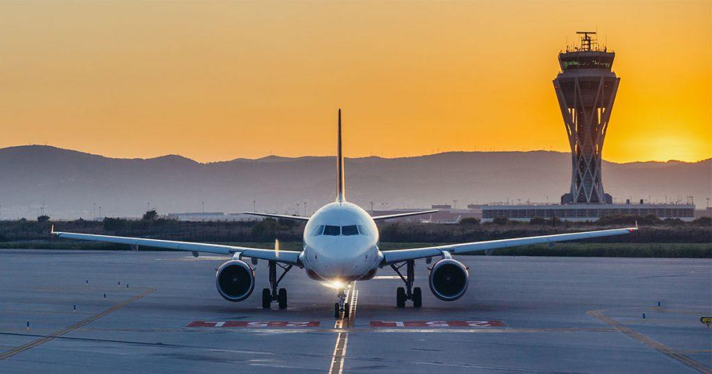 Un avión sobre la plataforma del aeropuerto de Barcelona. Al fondo, la torre de control.
